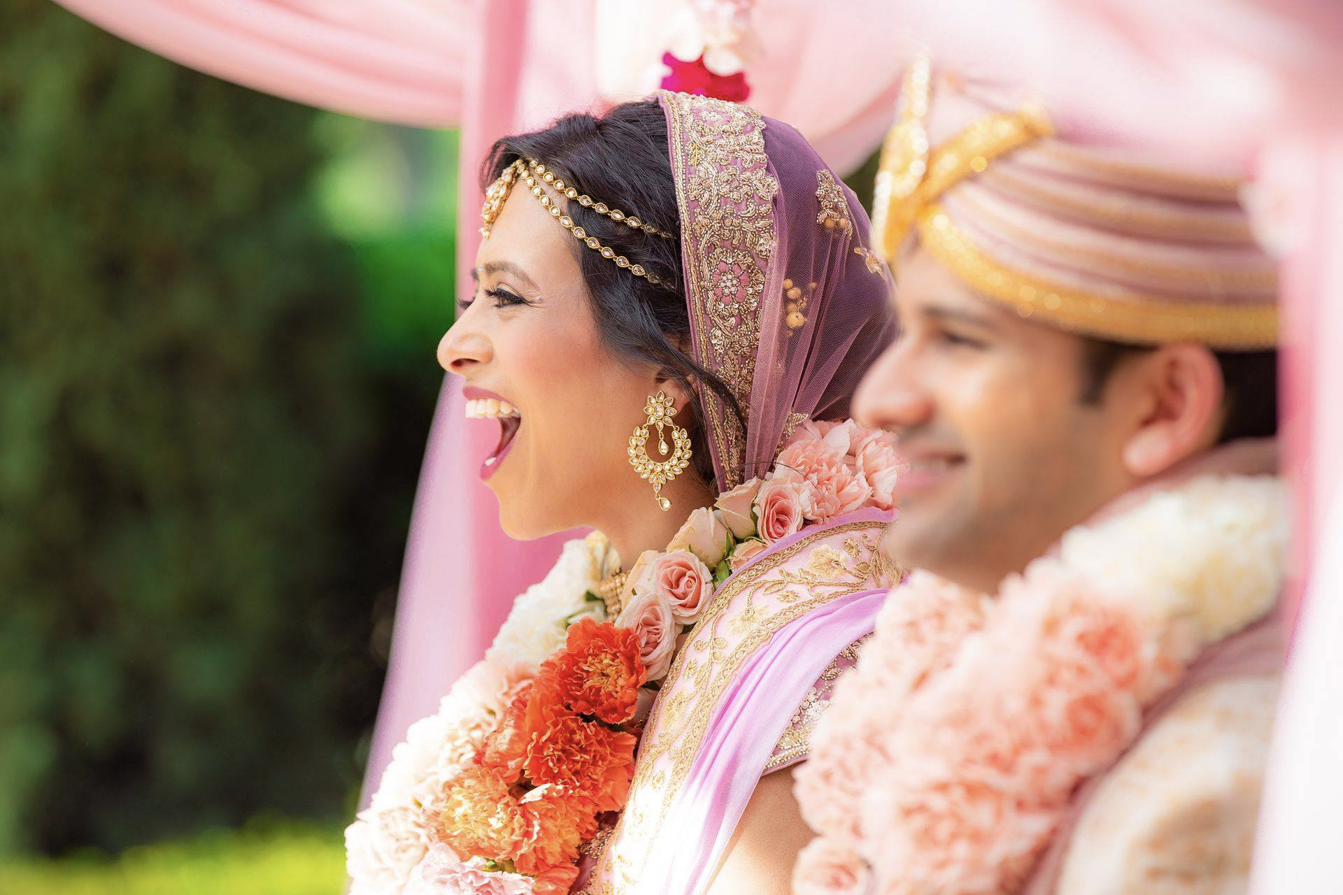 Close up portrait of an Indian couple smiling and cheering after getting married