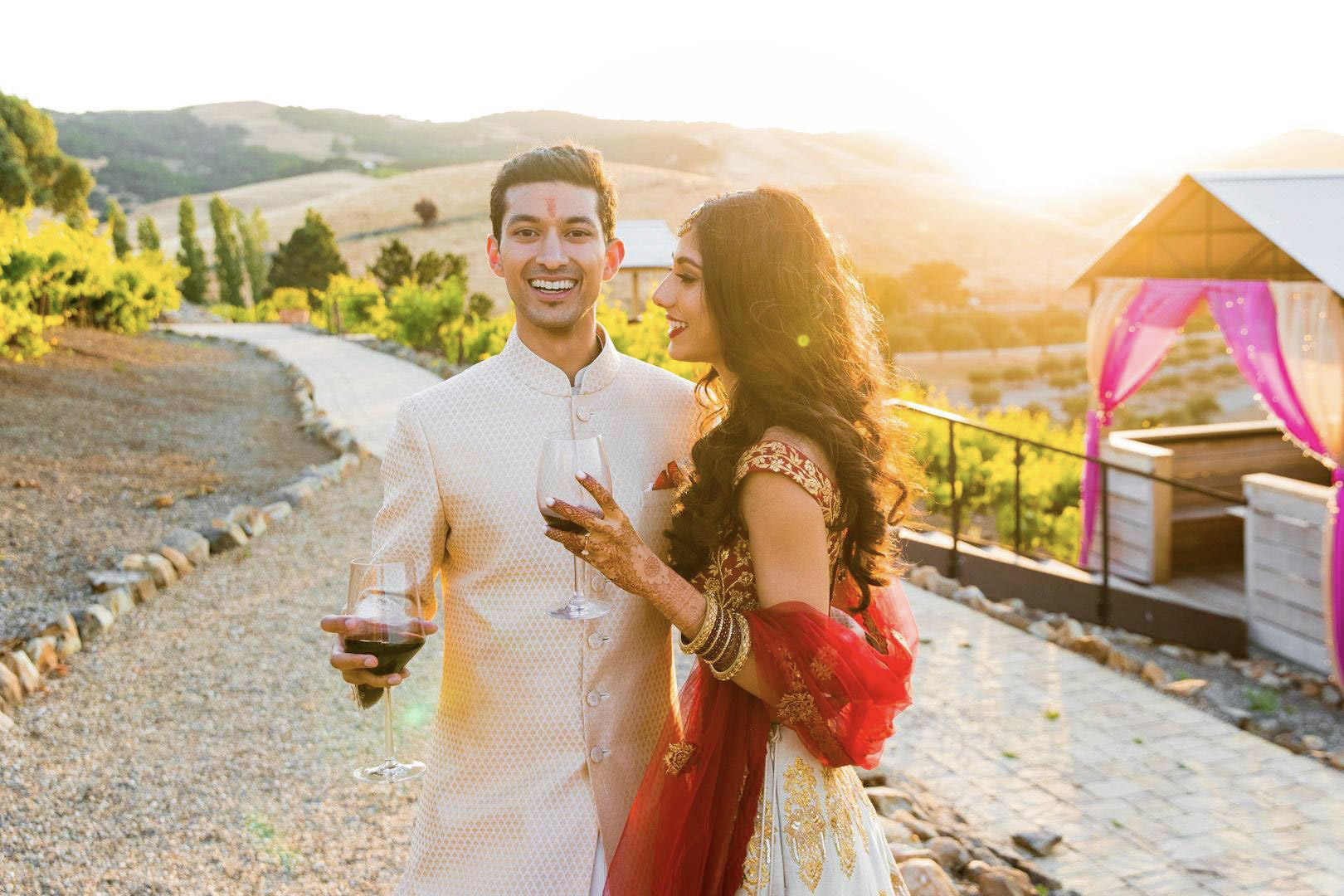 Indian couples posing in a pre-wedding event while holding wine