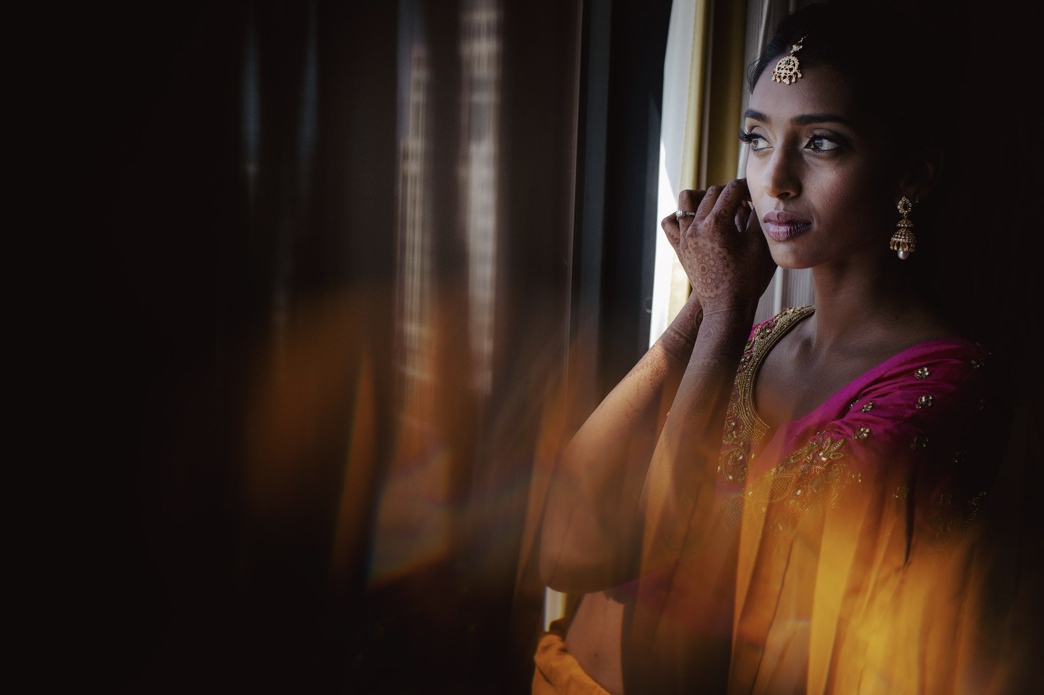 Mid angle shot of an Indian bride getting ready and wearing earrings in front of a window