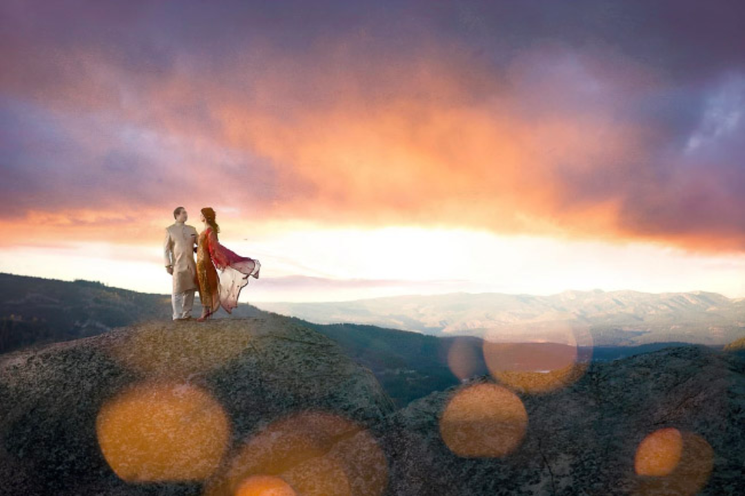 Bride and groom dressed in traditional Indian wedding clothes posing on top of a cliff