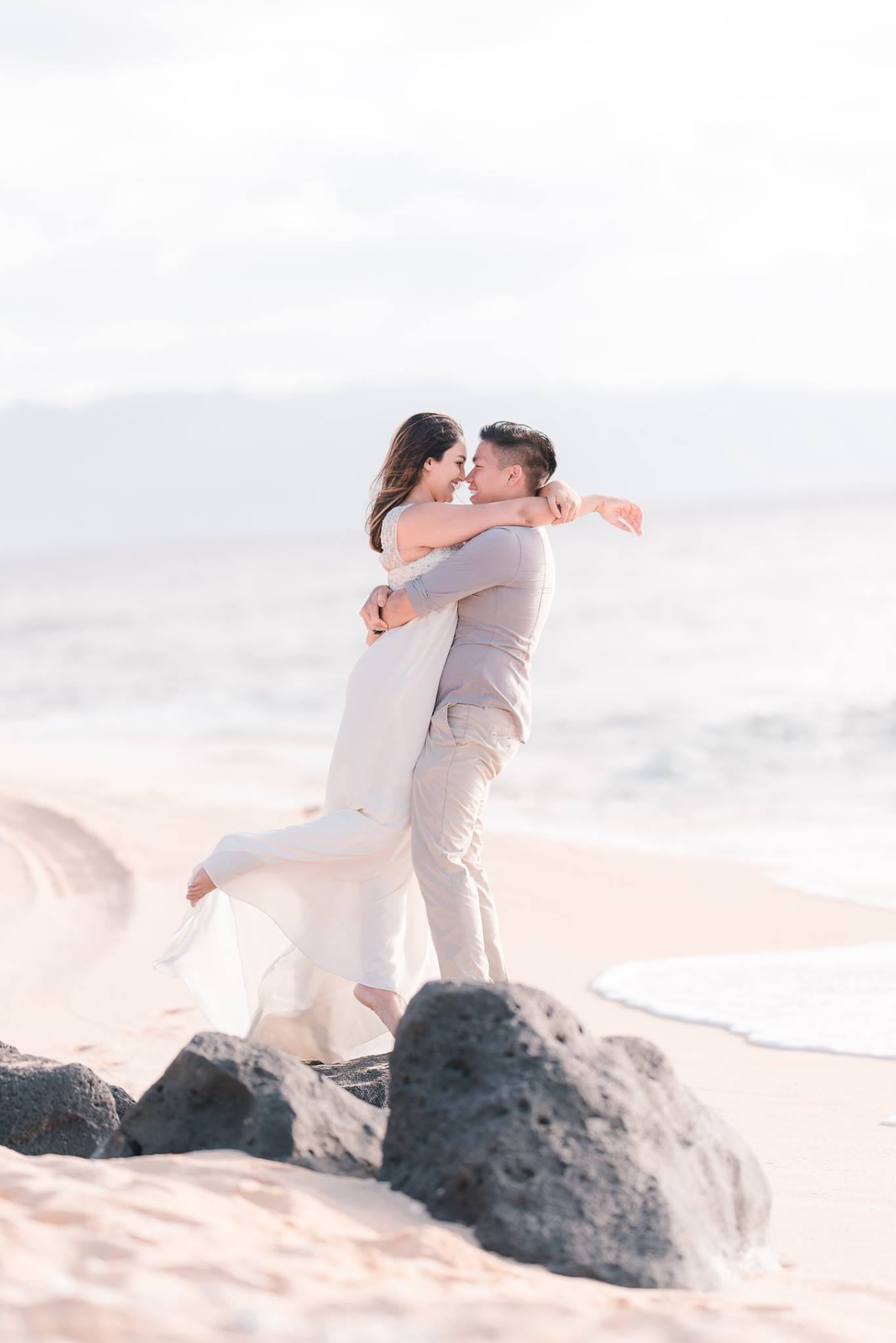 A couple holding each other as they pose by the beach