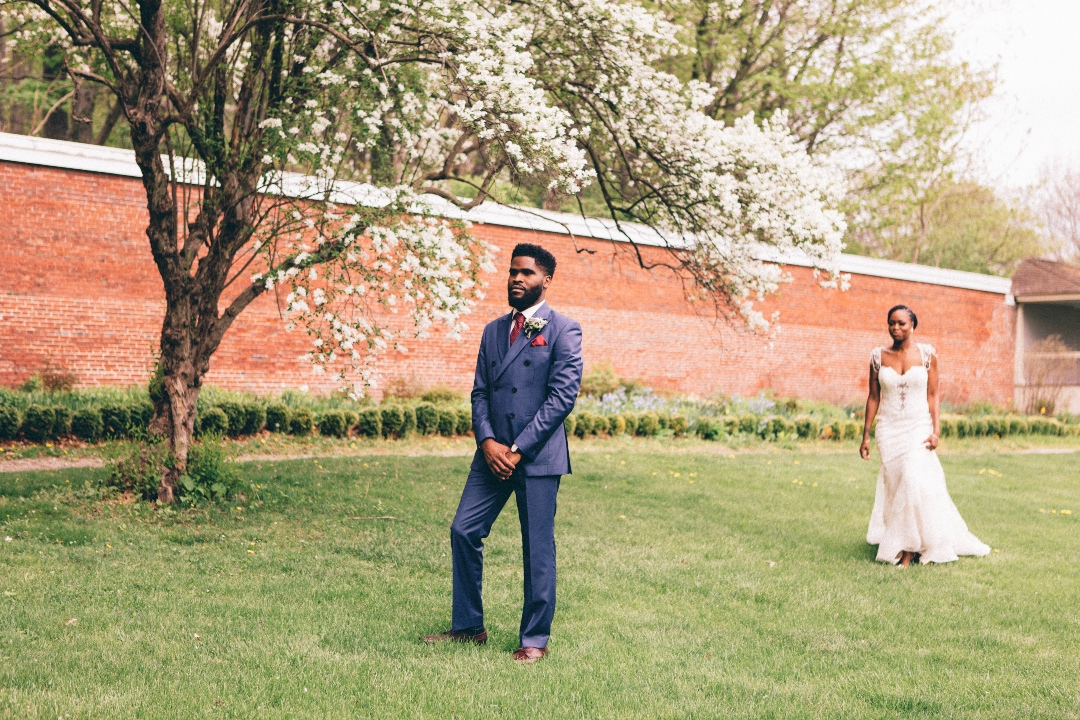 A groom looking towards the camera just as the bride walks up to him from behind for the first look moment in a garden