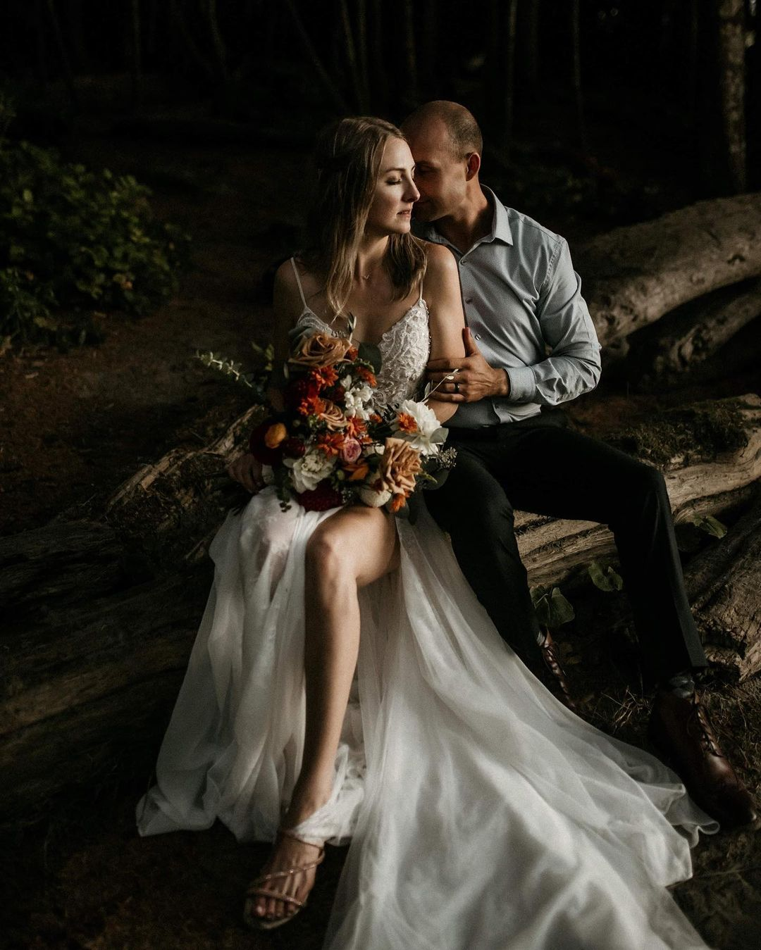 A bride and groom posing facing each other while being seated on a log