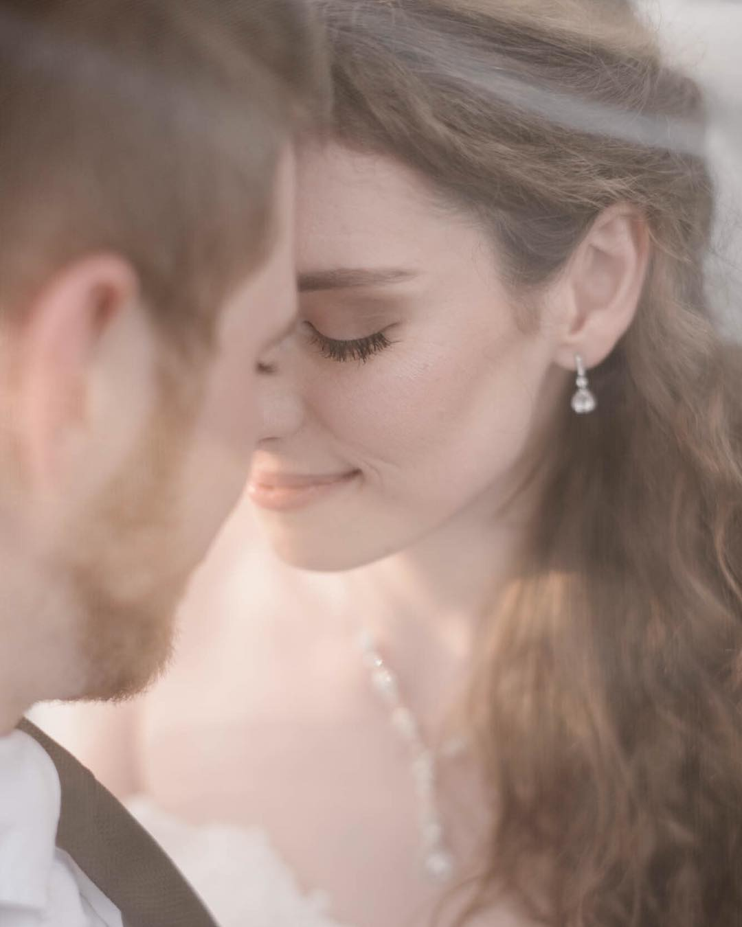 A close up portrait of a bride and groom smiling and leaning their foreheads on each other