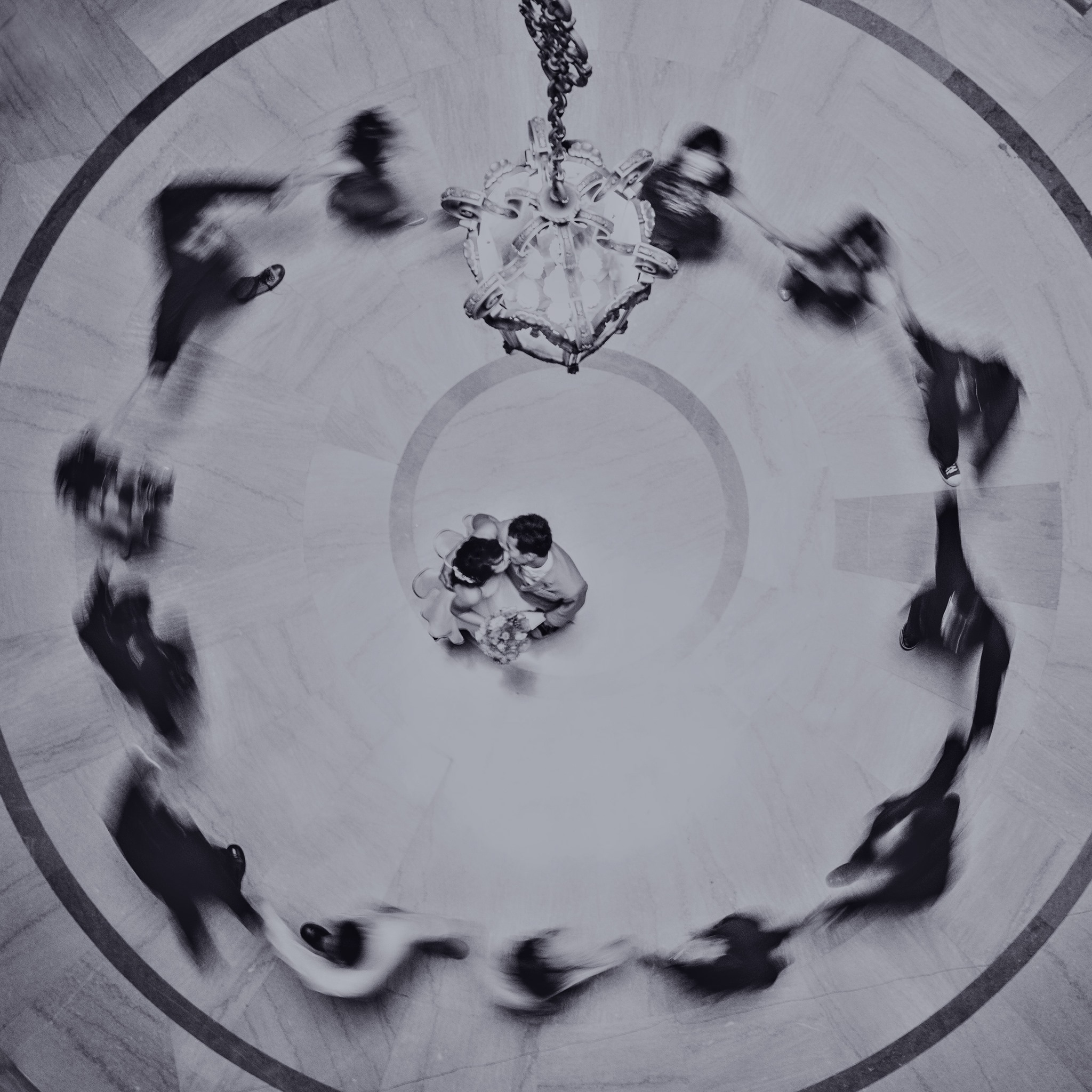 A bird eye's view of a couple dancing at the center of a circle created by the bridesmaid and groomsmen
