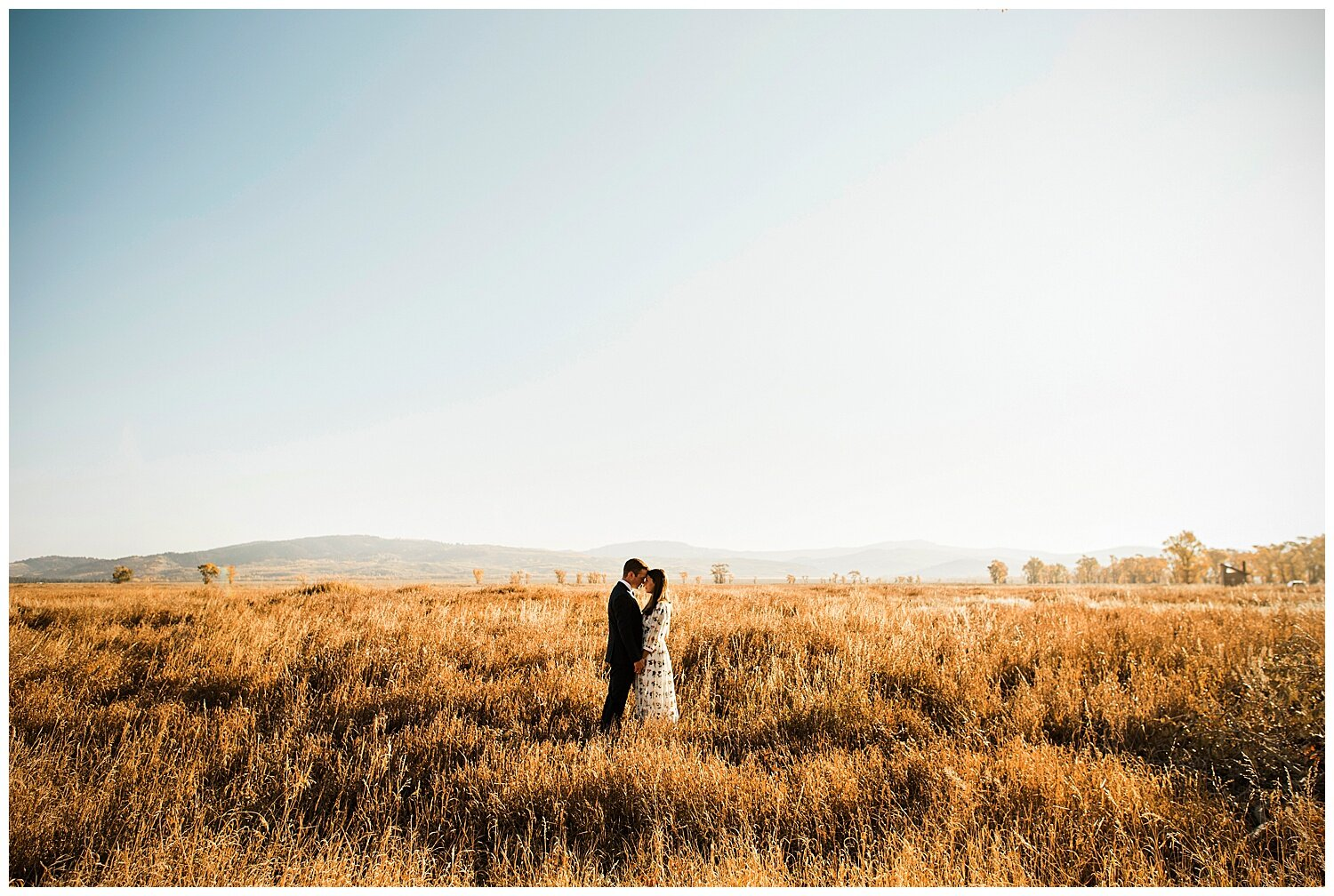 A couple posing for a picture while holding each other's hand in a middle of a field with sky as the background