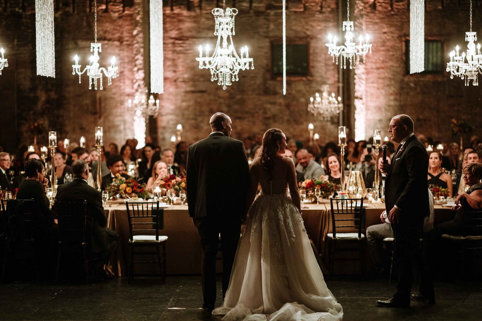 A bride and groom standing beside the banquet table as a guest is giving a toast