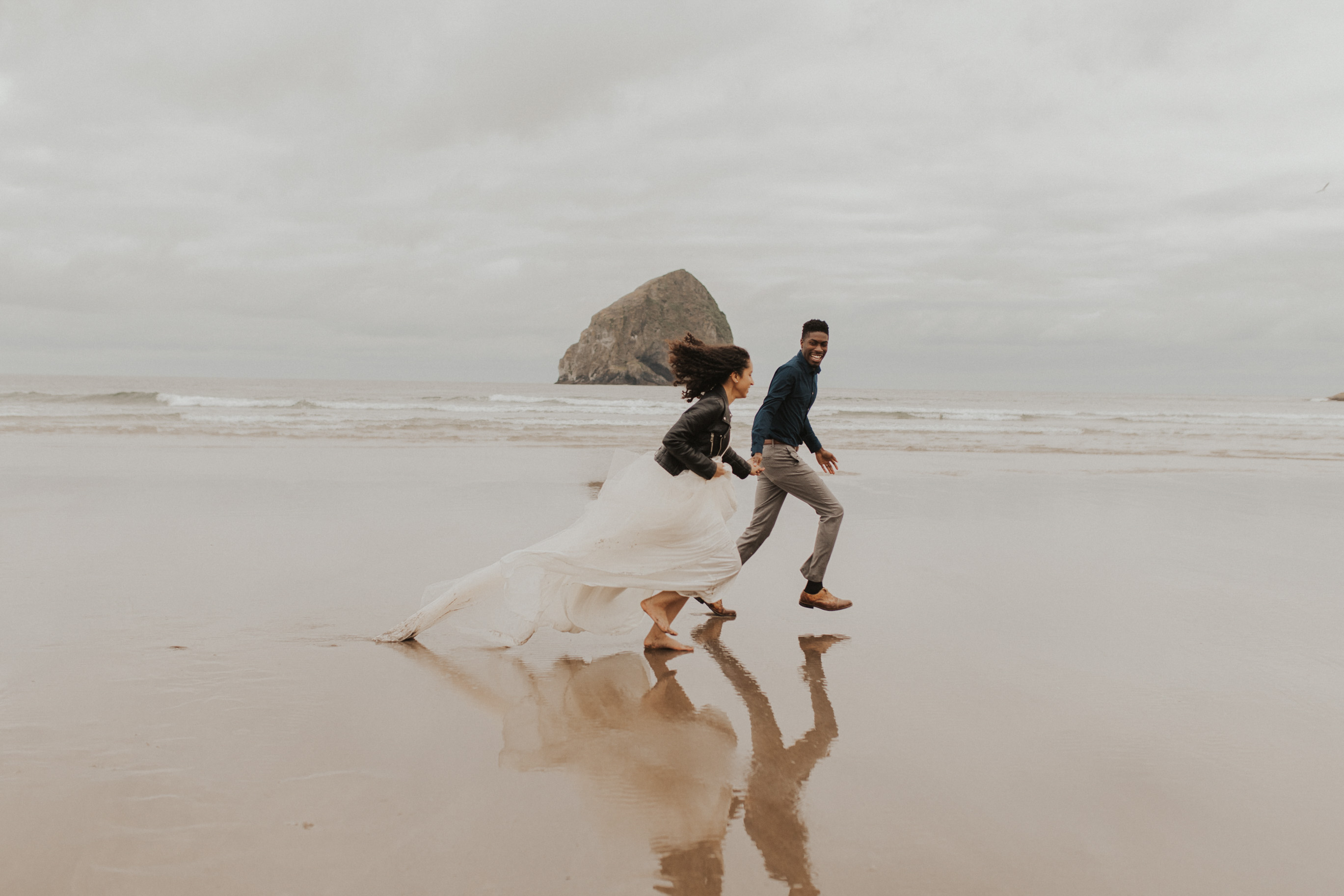 A bride and groom running on the beach as the waves crash at the background