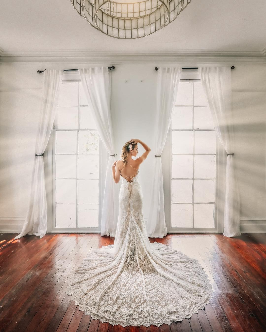 A bride posing in front of two windows flaunting the train of her wedding dress