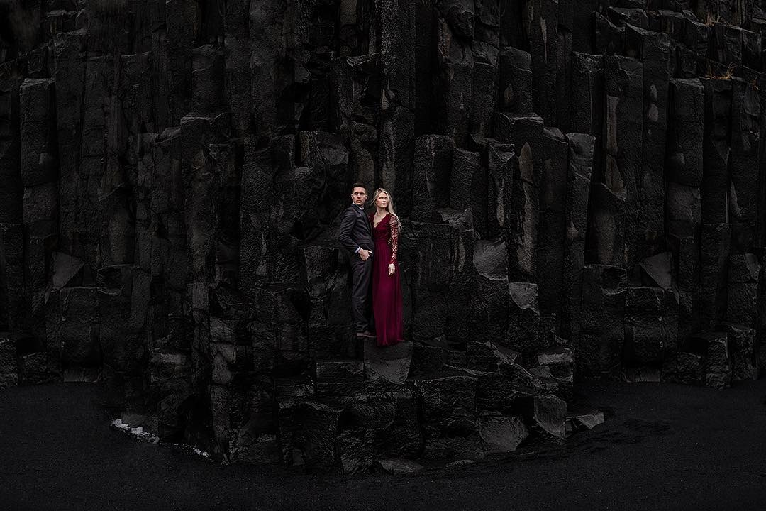 A couple posing while standing in between a black-colored rock formation