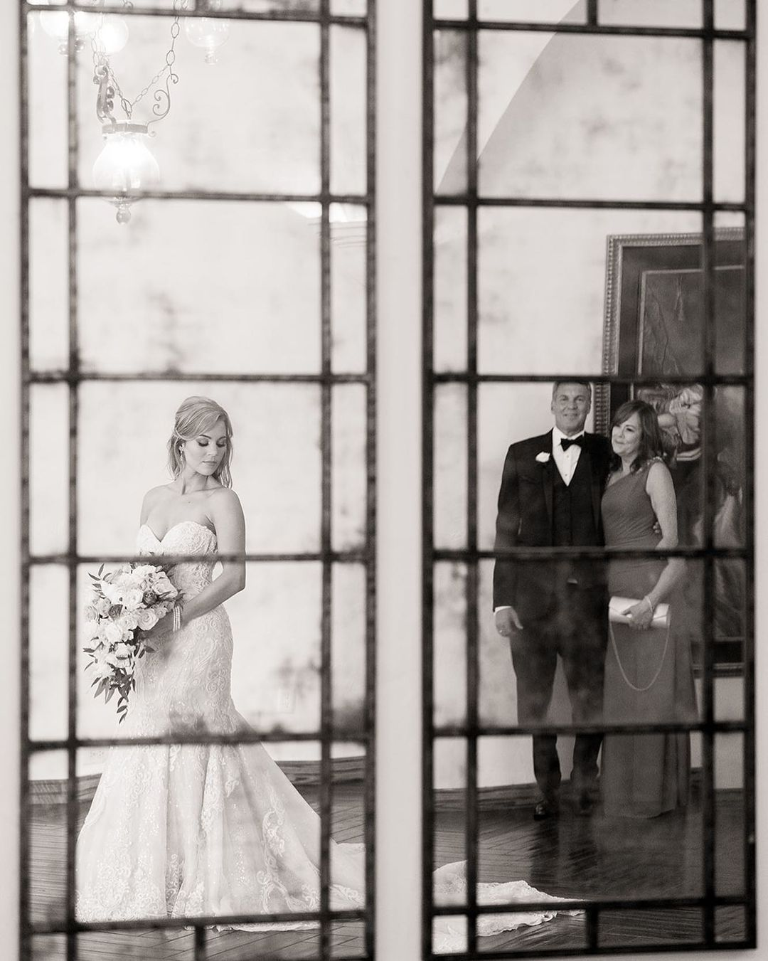Black and white image from the POV of a window of a bride holding her bridal bouquet as her parents look emotionally from a distance