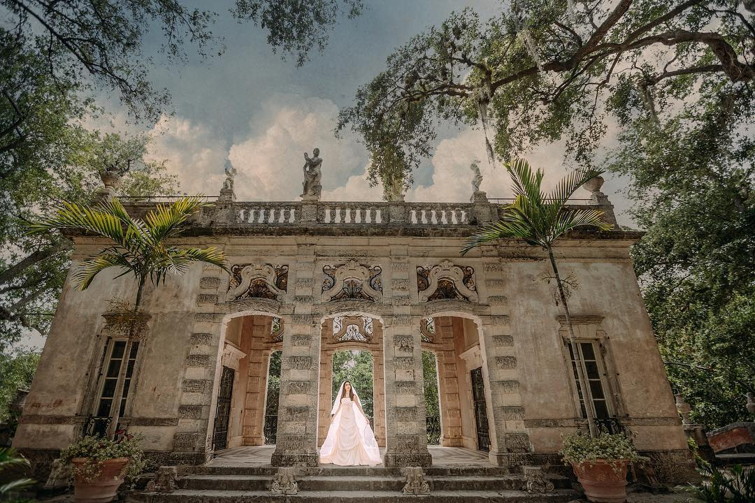 A wide-angle shot of a bride standing at the doorway of a beautiful wedding venue