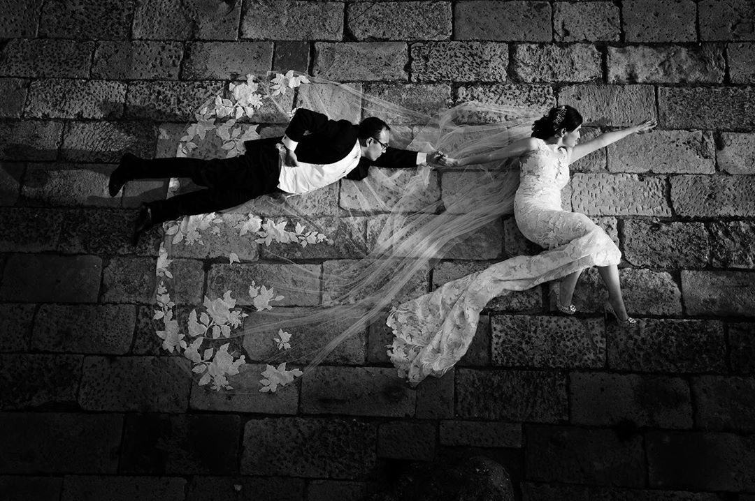 Black and white photograph of a bride and groom posing to be superheroes