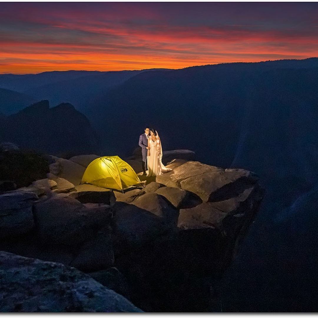 A couple posing near a camp while standing on top of a cliff during sunset