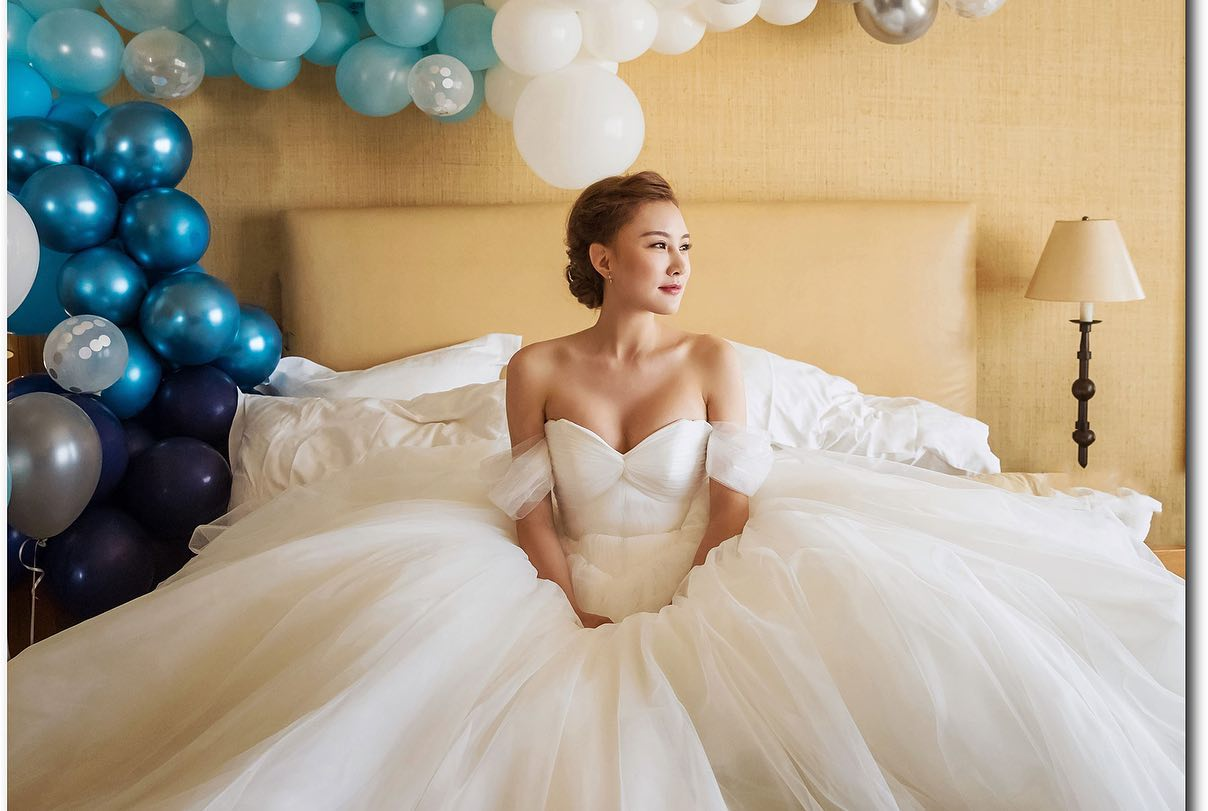 Portrait of a bride sitting on the bed with blue color balloons in the background