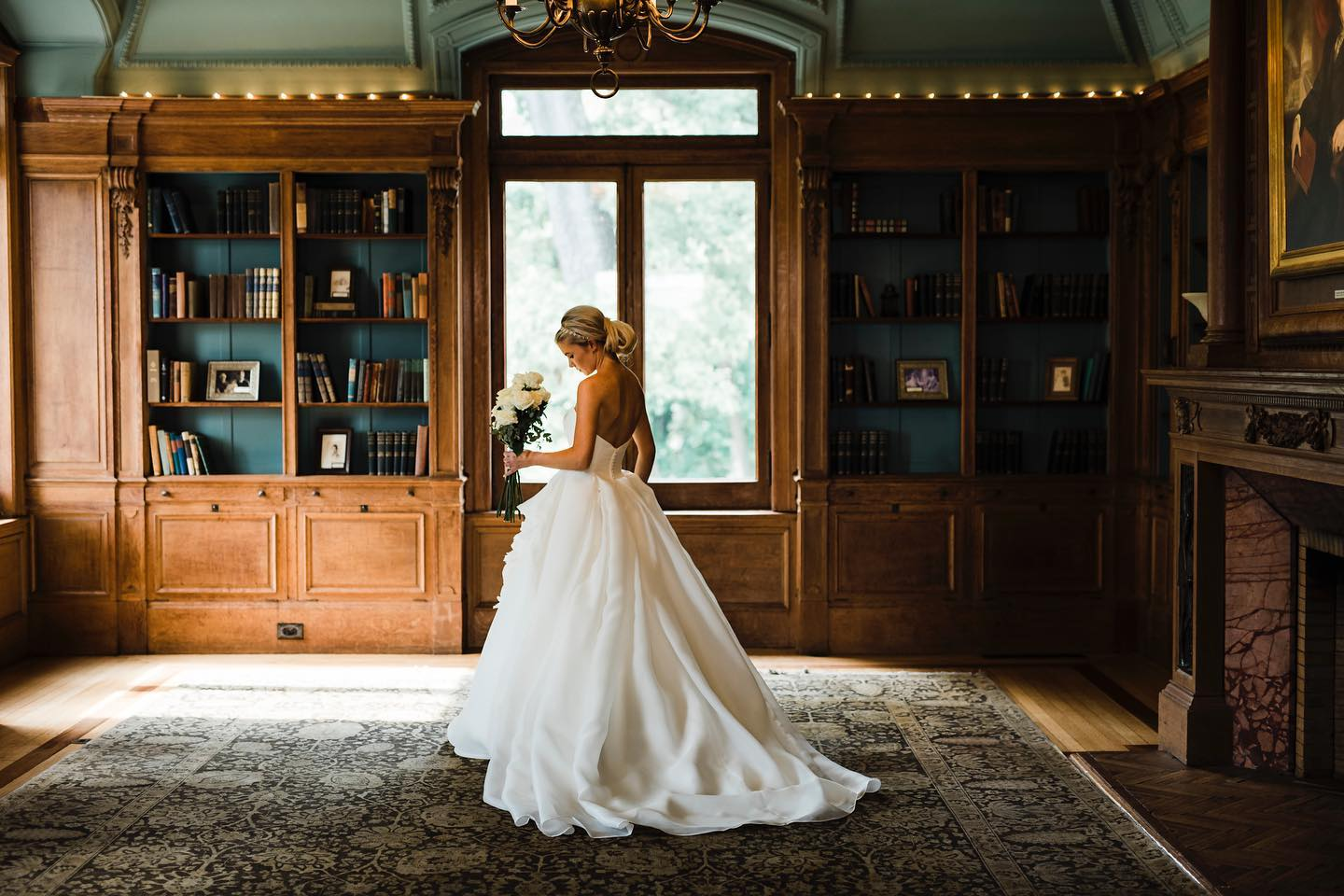 A portrait of a bride posing in front of a window in a vintage-themed room