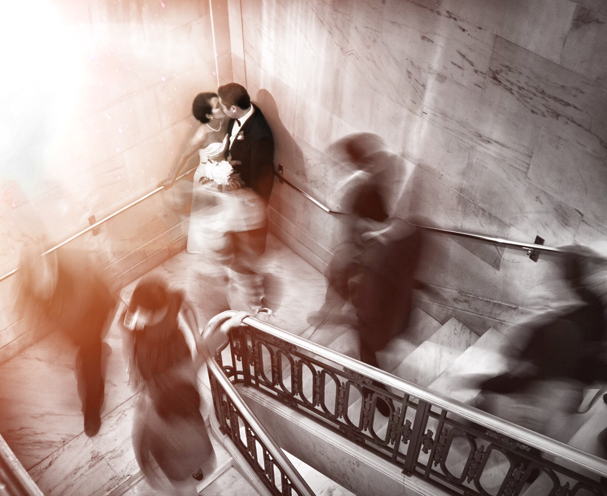 A bride and groom kissing at the corner of a stairway as the guests are captured in a blur as they walk around