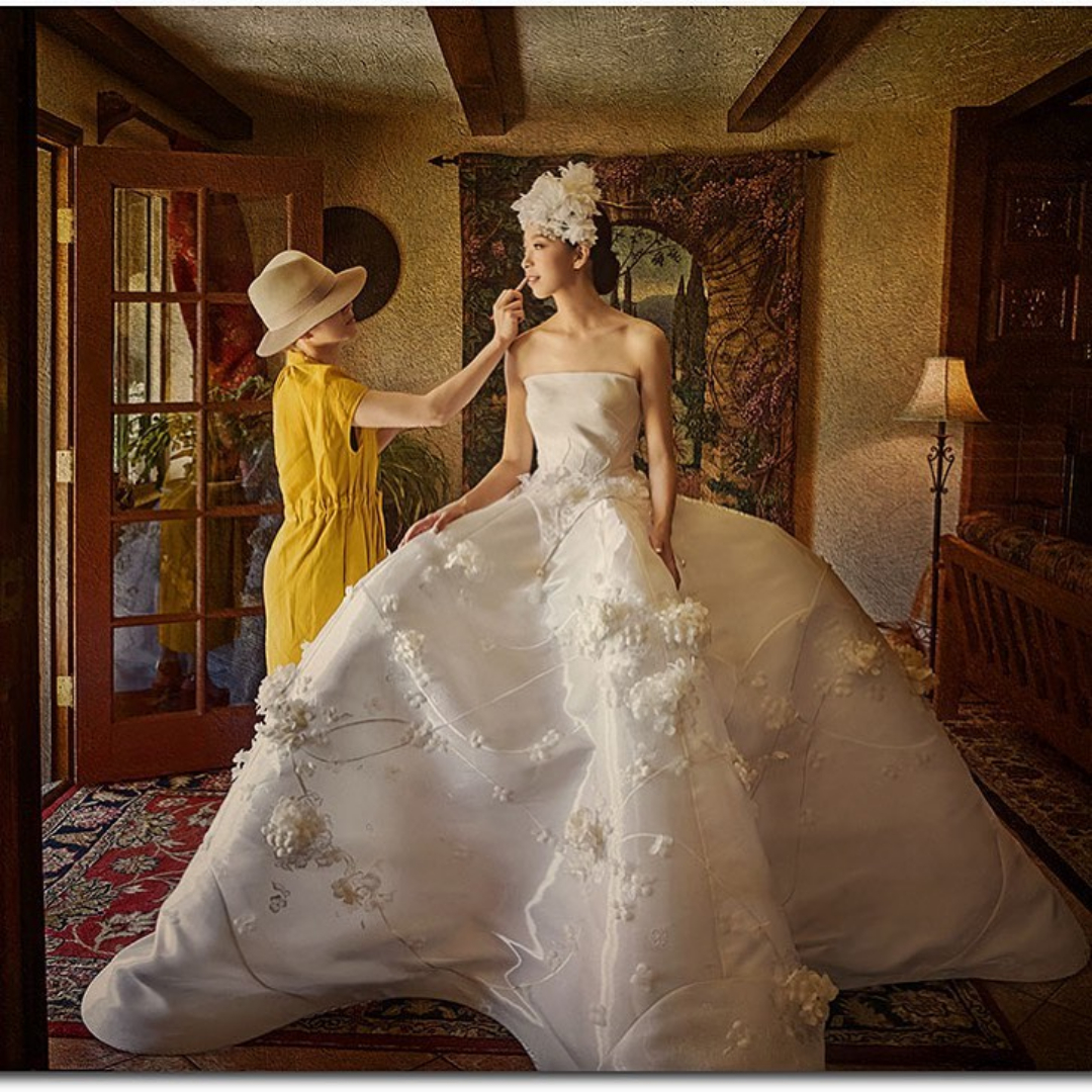 A bride stands in front of a doorway as the makeup artist fixes her makeup