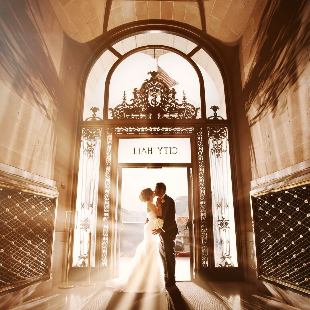 A bride and groom kissing at a doorway entrance of a city hall