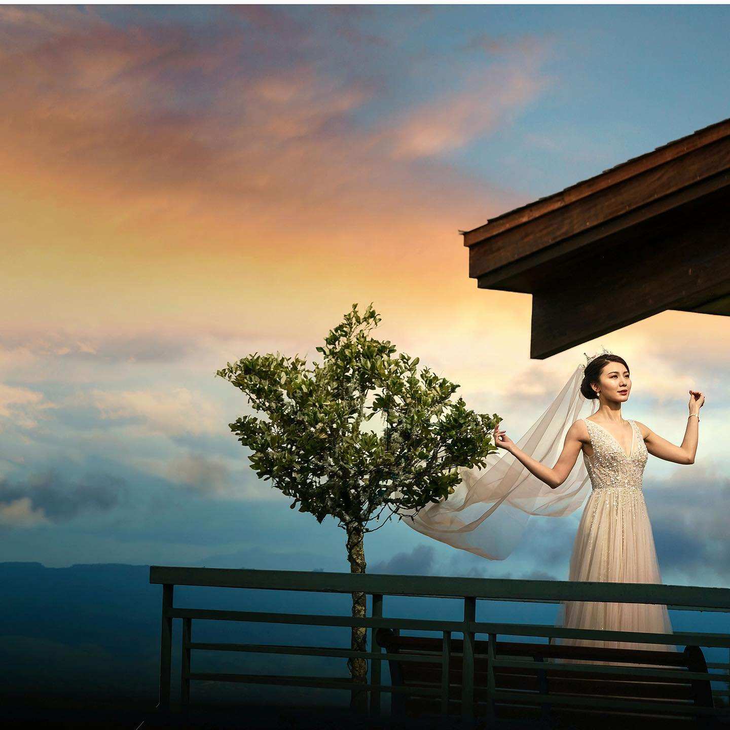 A bride standing at a balcony while posing with her veil during the blue hour