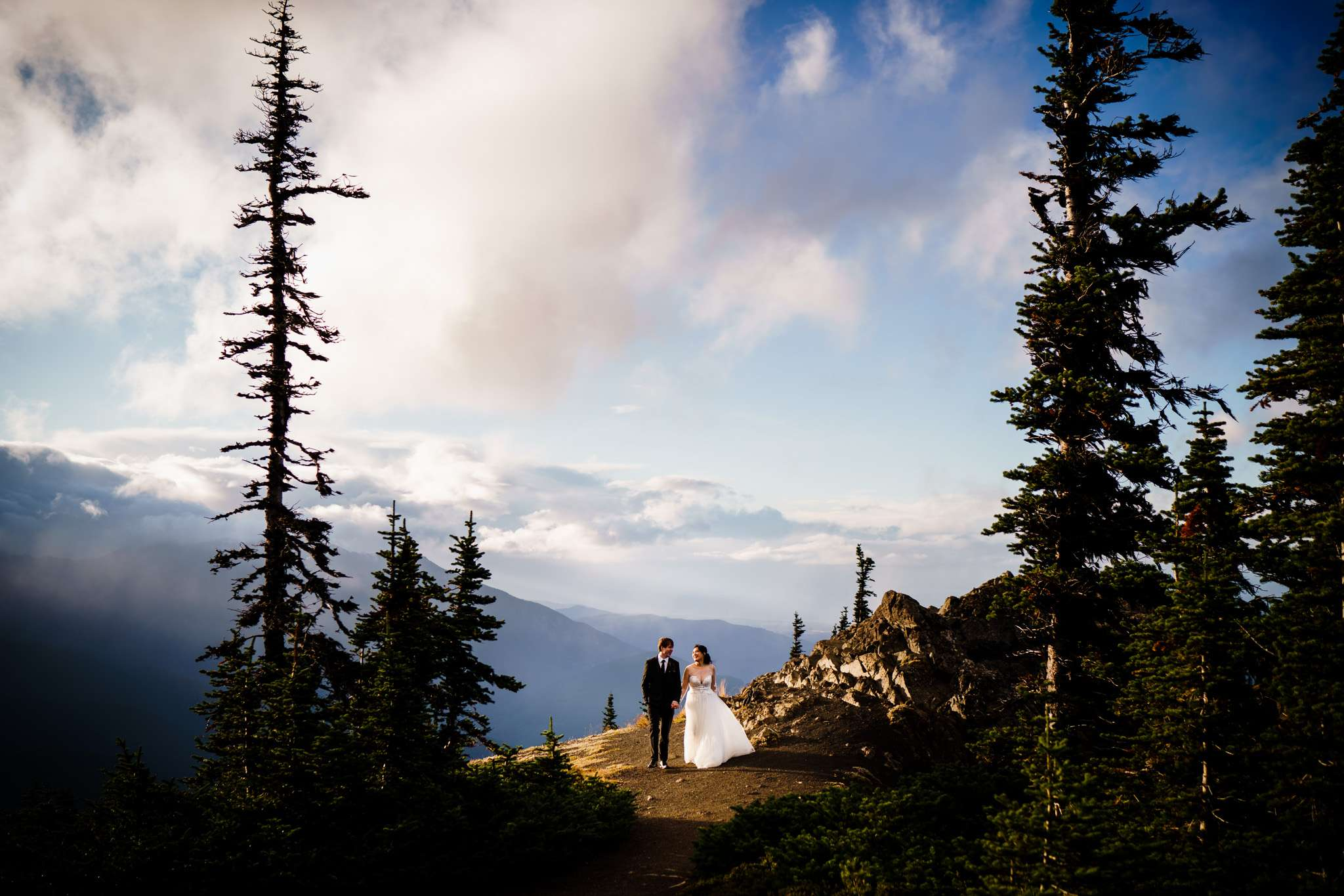 A bride and groom holds hands on top of a mountain top with cloud-covered mountain peaks at the background
