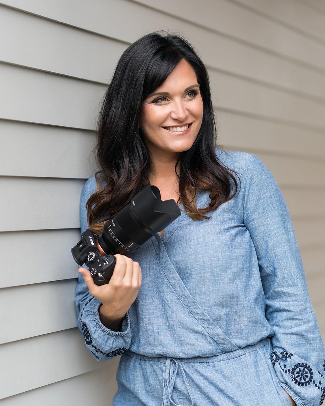 A portrait of Sara France holding a Sony  camera