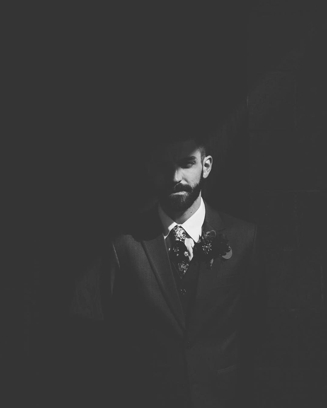 A monochrome portrait of a groom standing beside a wall as half of his face is in shade