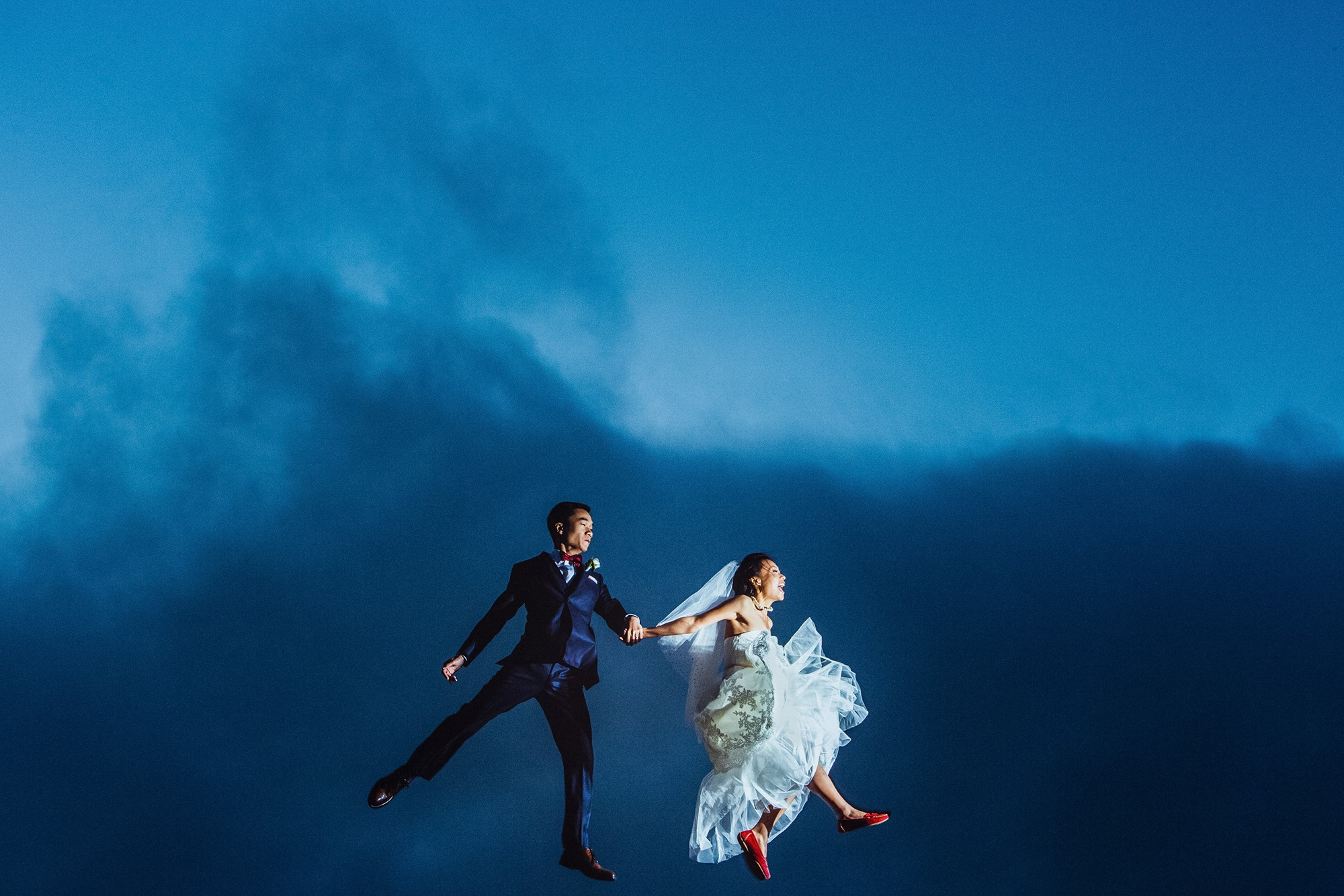 A bride and groom holding hands while doing a jump shot