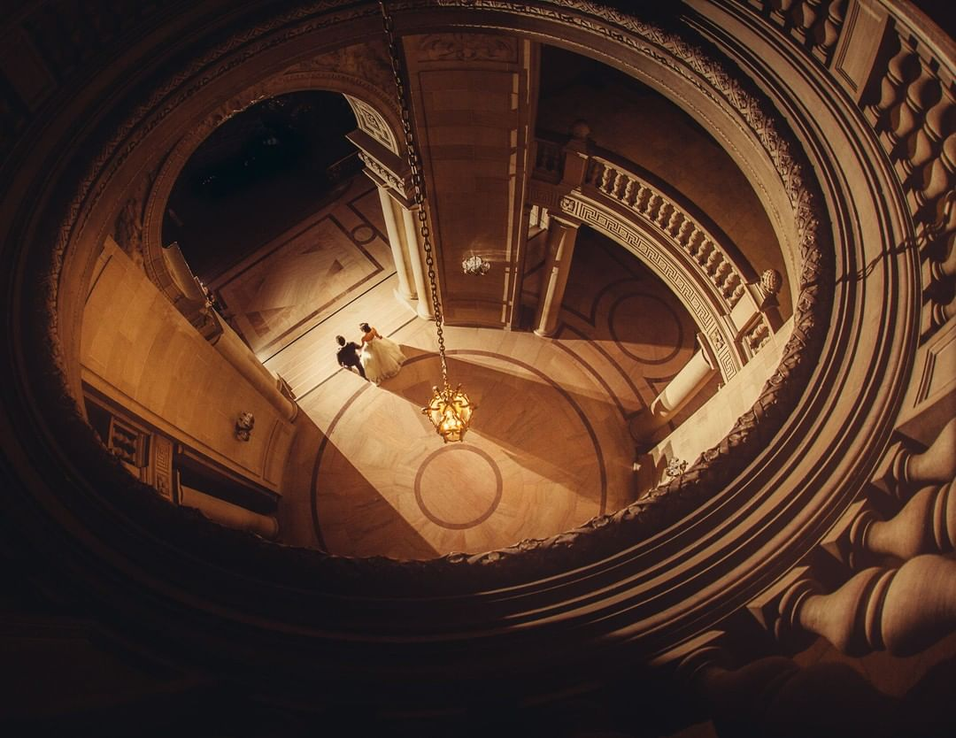 High-angle view of a bride and groom walking towards the doorway of a spiral auditorium
