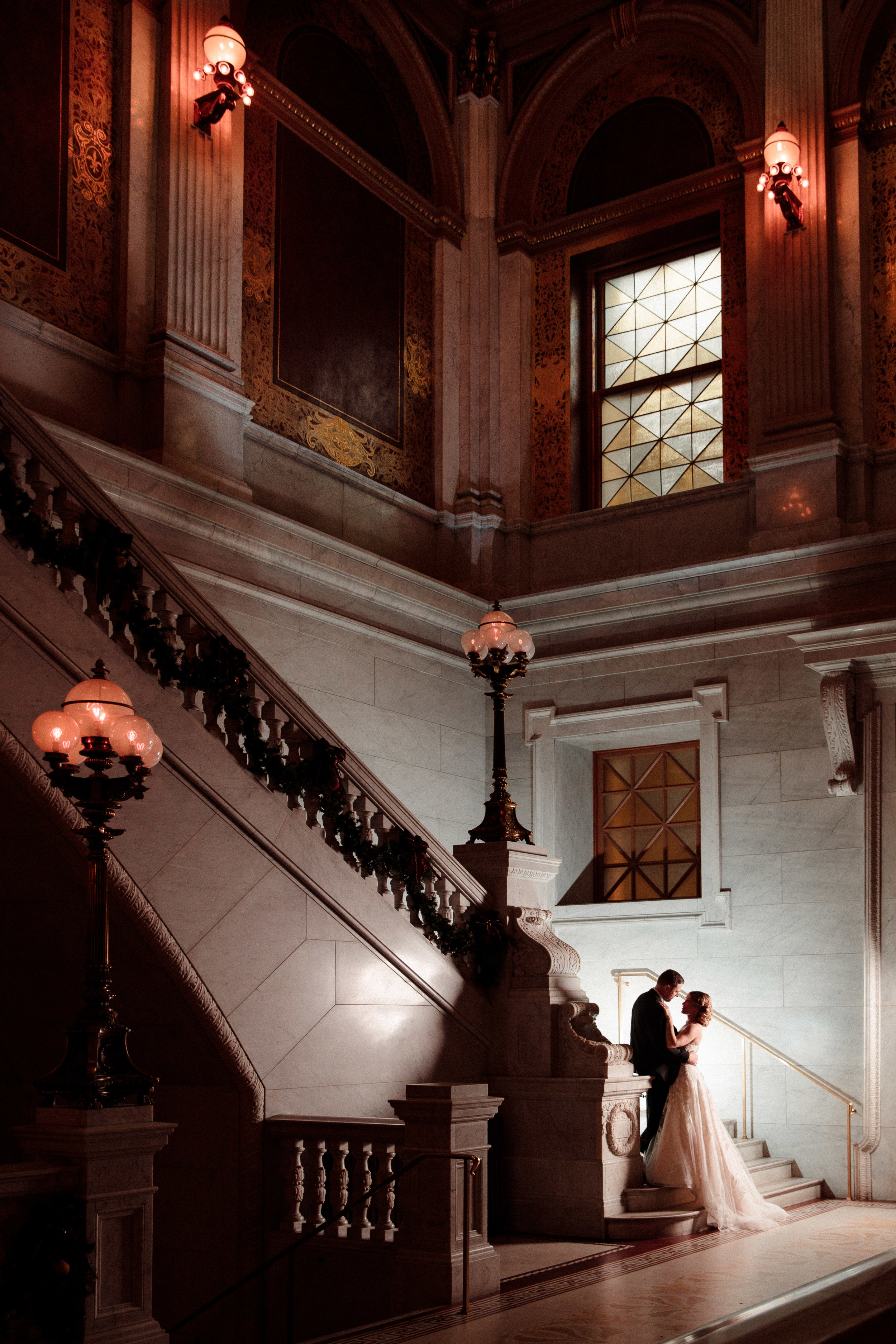 A bride and groom posing at the edge of a stairway while looking into each other's eyes