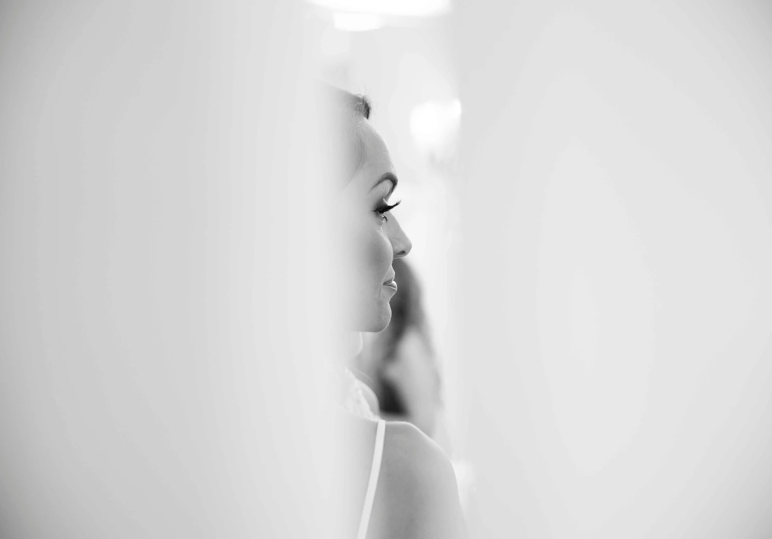 Black and white portrait of a bride through a peek in between two walls