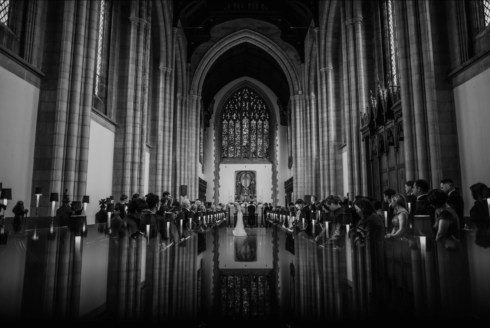 Black and white photo of a bride and groom and their guests during the wedding ceremony