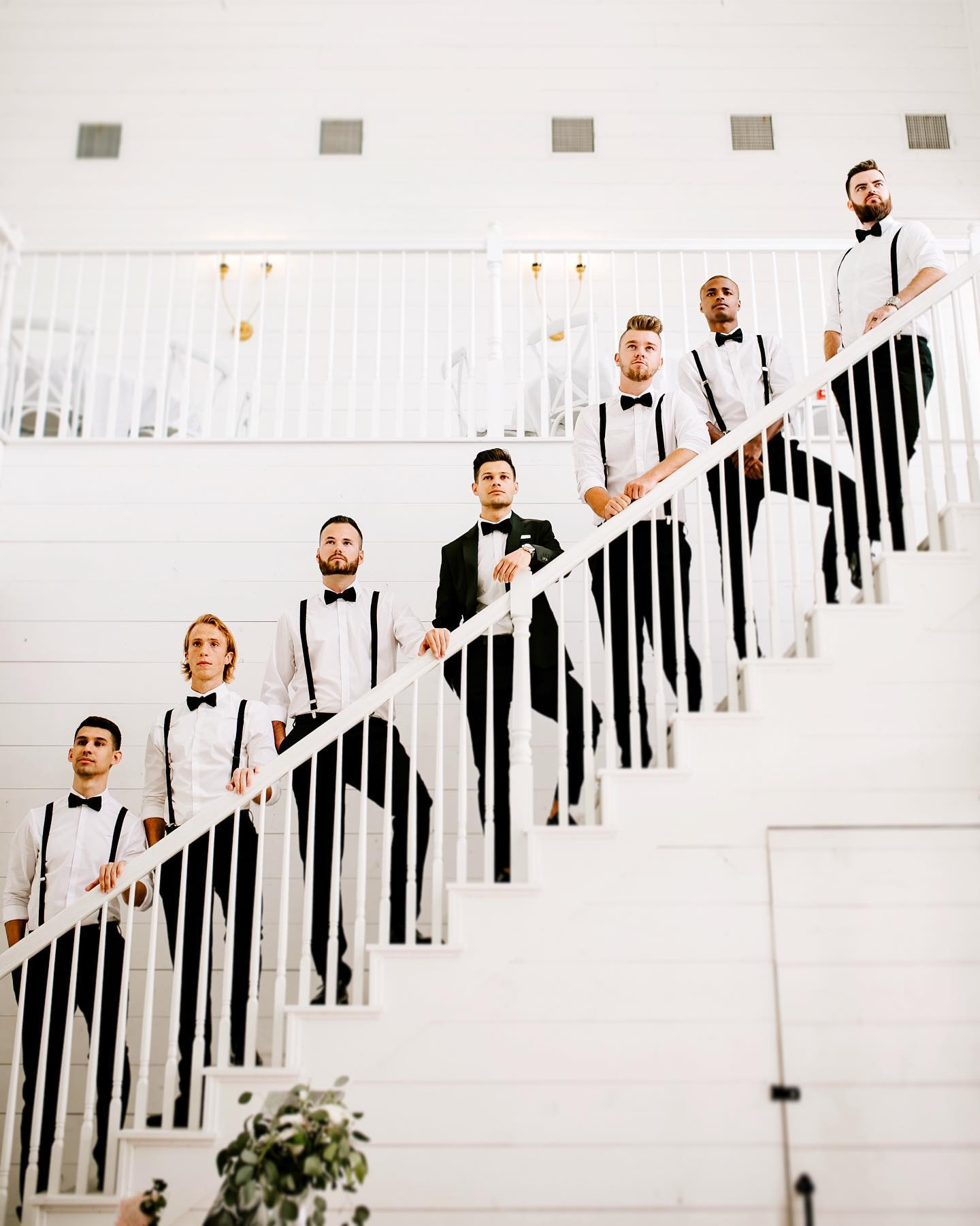Groom and groomsmen pose while standing on a white-colored stairway