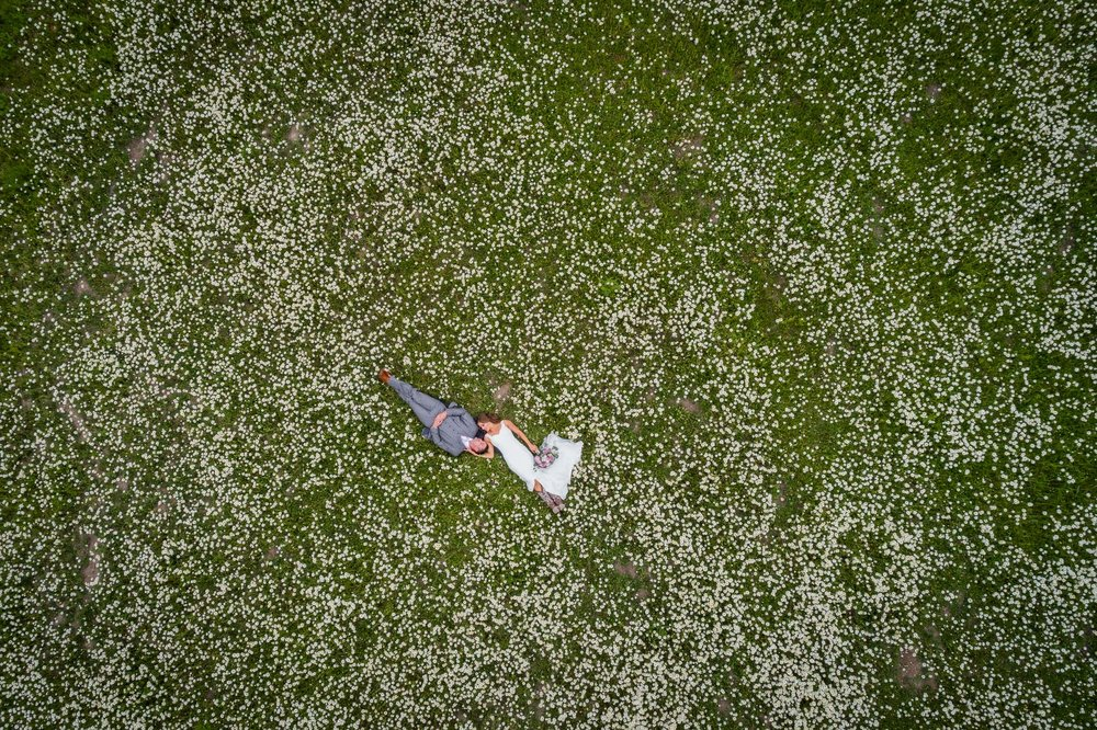 Aerial shot of a bride and groom lying on the field covered with white flowers