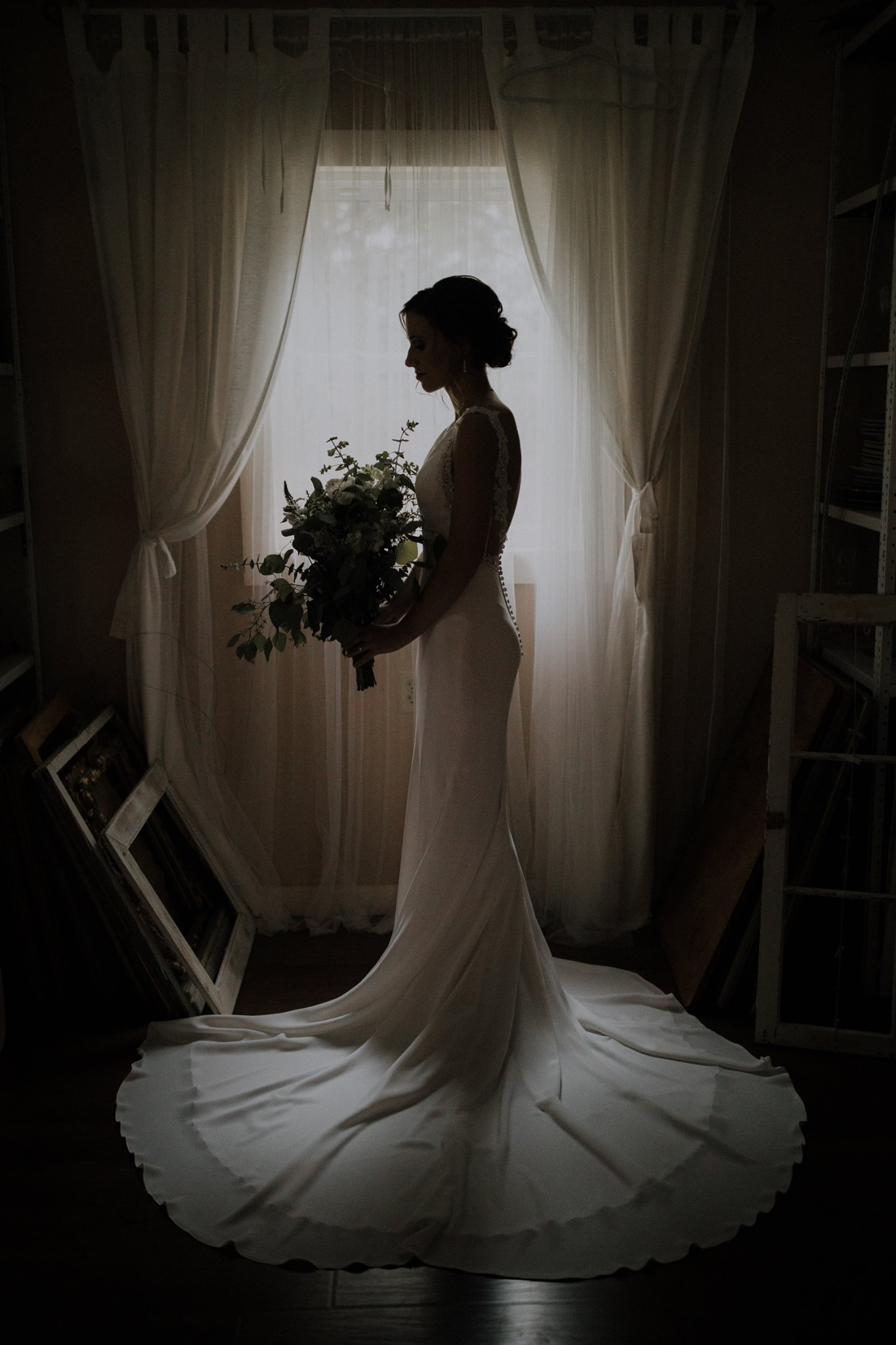 A silhouette of a bride posing in front of a window as she holds a bridal bouquet