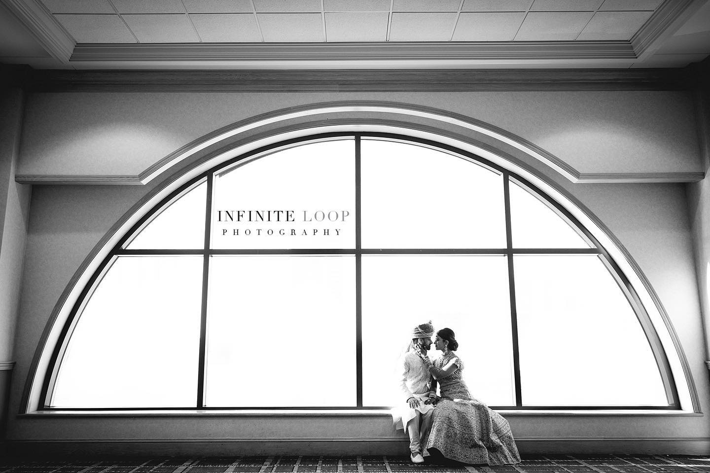 Black and white photo of a bride and groom dressed in traditional clothes pose in front of a semi-circle shaped window