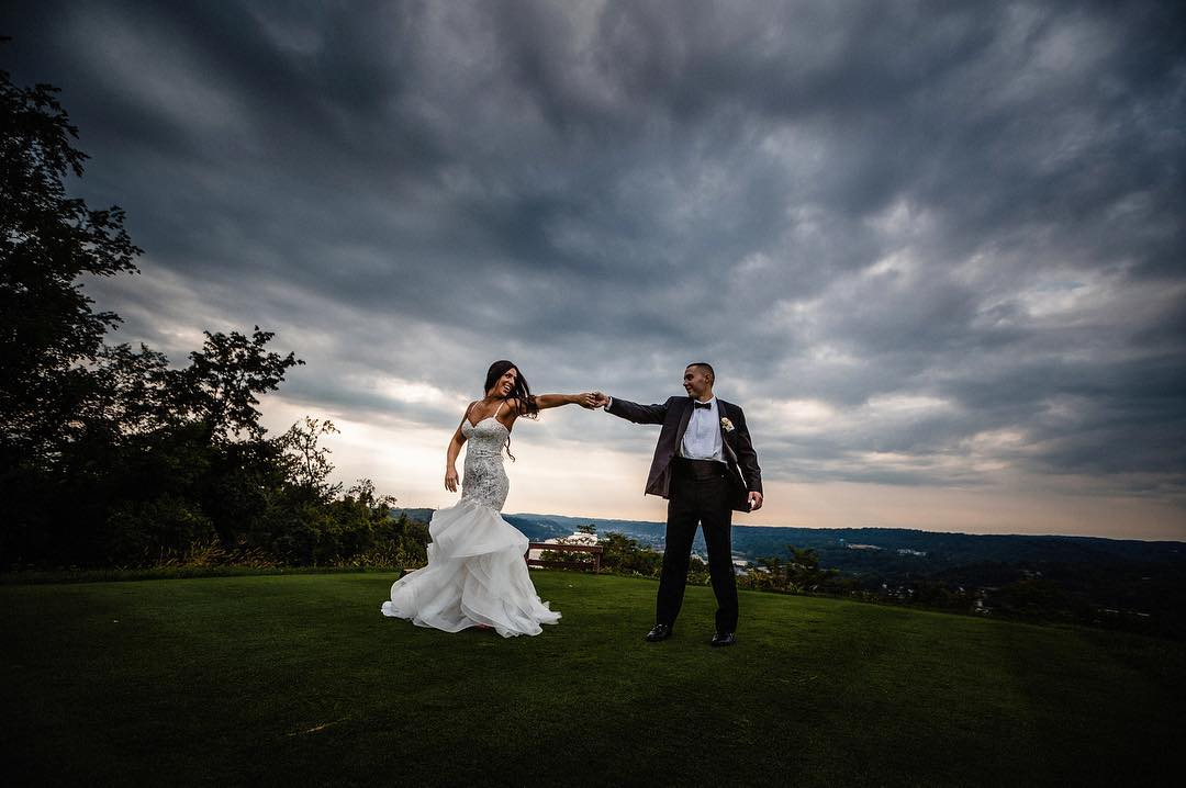 A bride and groom posing while holding hands
