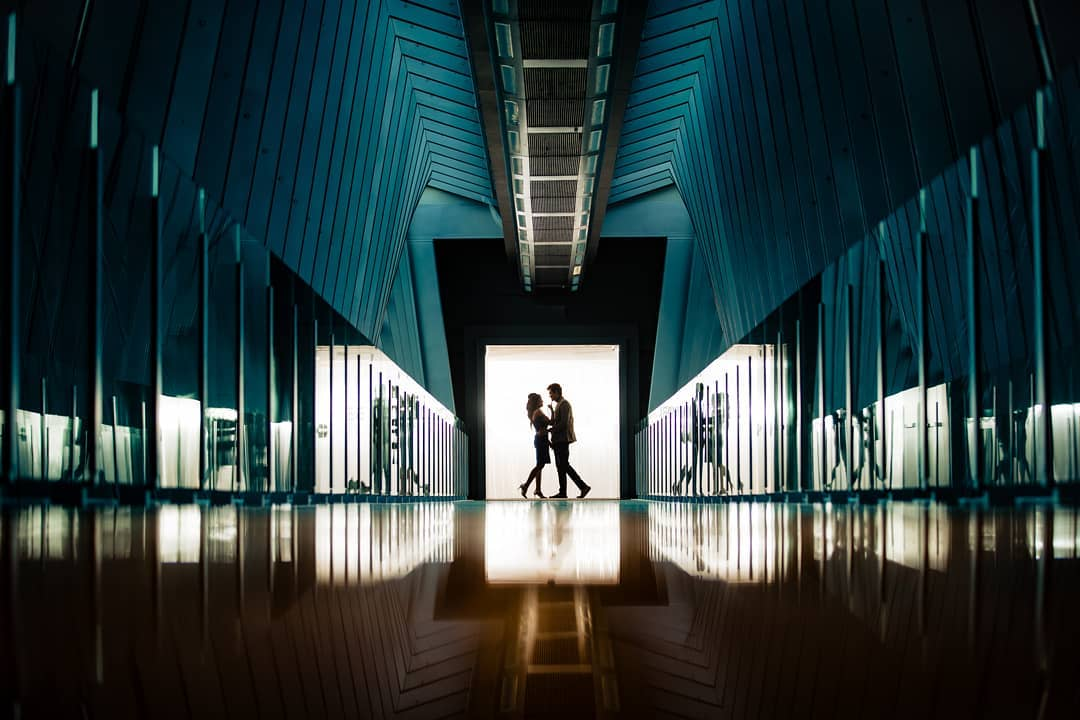 Silhouette of a couple facing each other  at the center of a door way of a blue-colored hallway with multiple lines