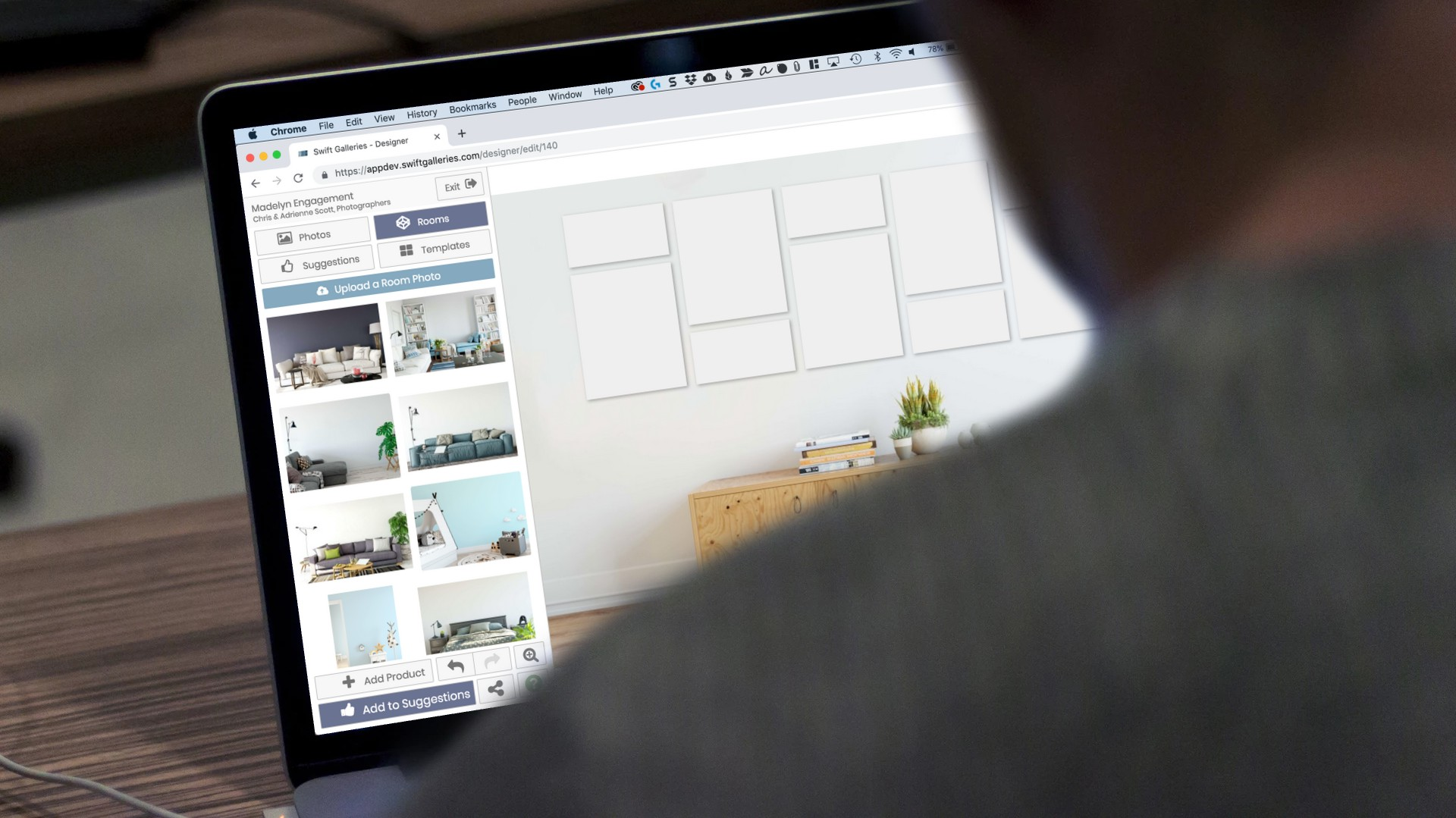 Over-the-shoulder shot of someone looking at the laptop while selecting Swift Galleries wall art templates