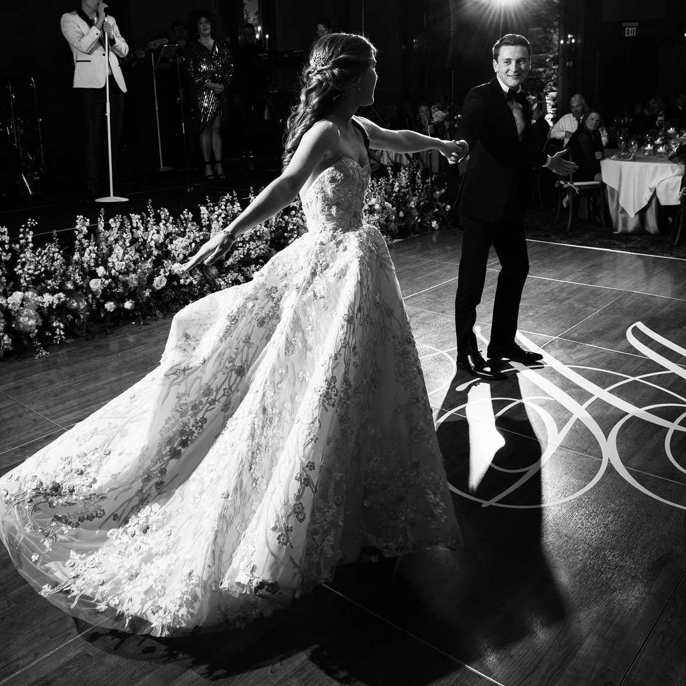 Black and white photo of a bride and groom dancing on the dance floor at the wedding reception