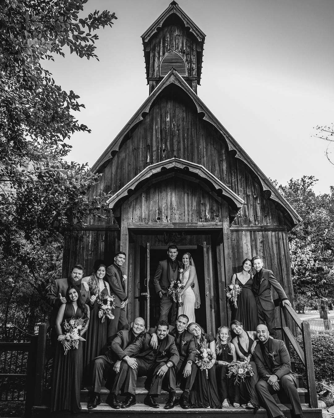 Black and white image of a couple and the bridesmaids and groomsmen posing at the entrance of a building