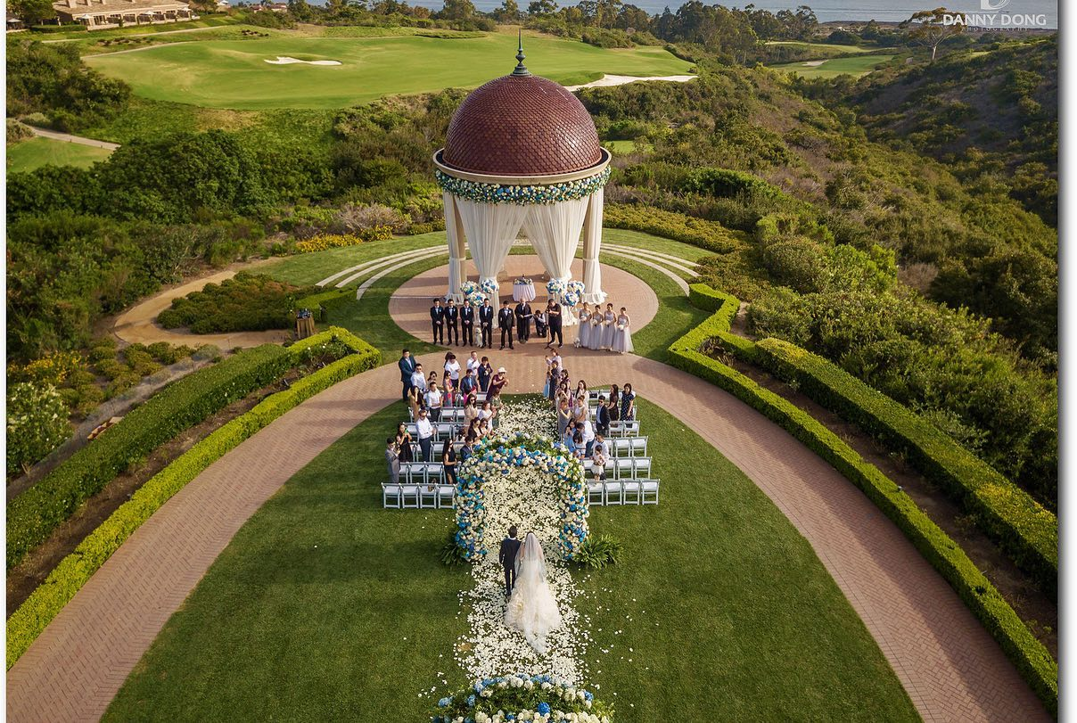 Bird's-eye view of a couple walking down the aisle at an outdoor wedding ceremony