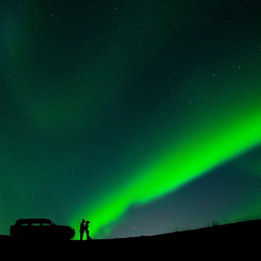 Silhouette of a couple looking at each other alongside a car under the sky full of stars and northern lights