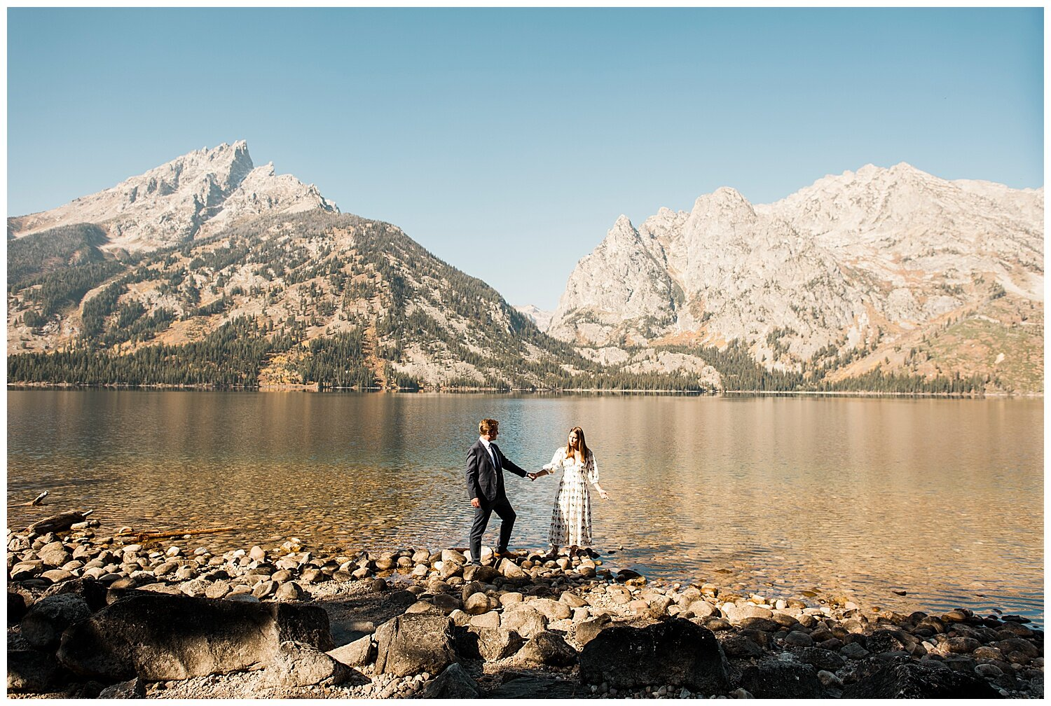 A couple holding hands while posing at the side of a lake with mountains at the background