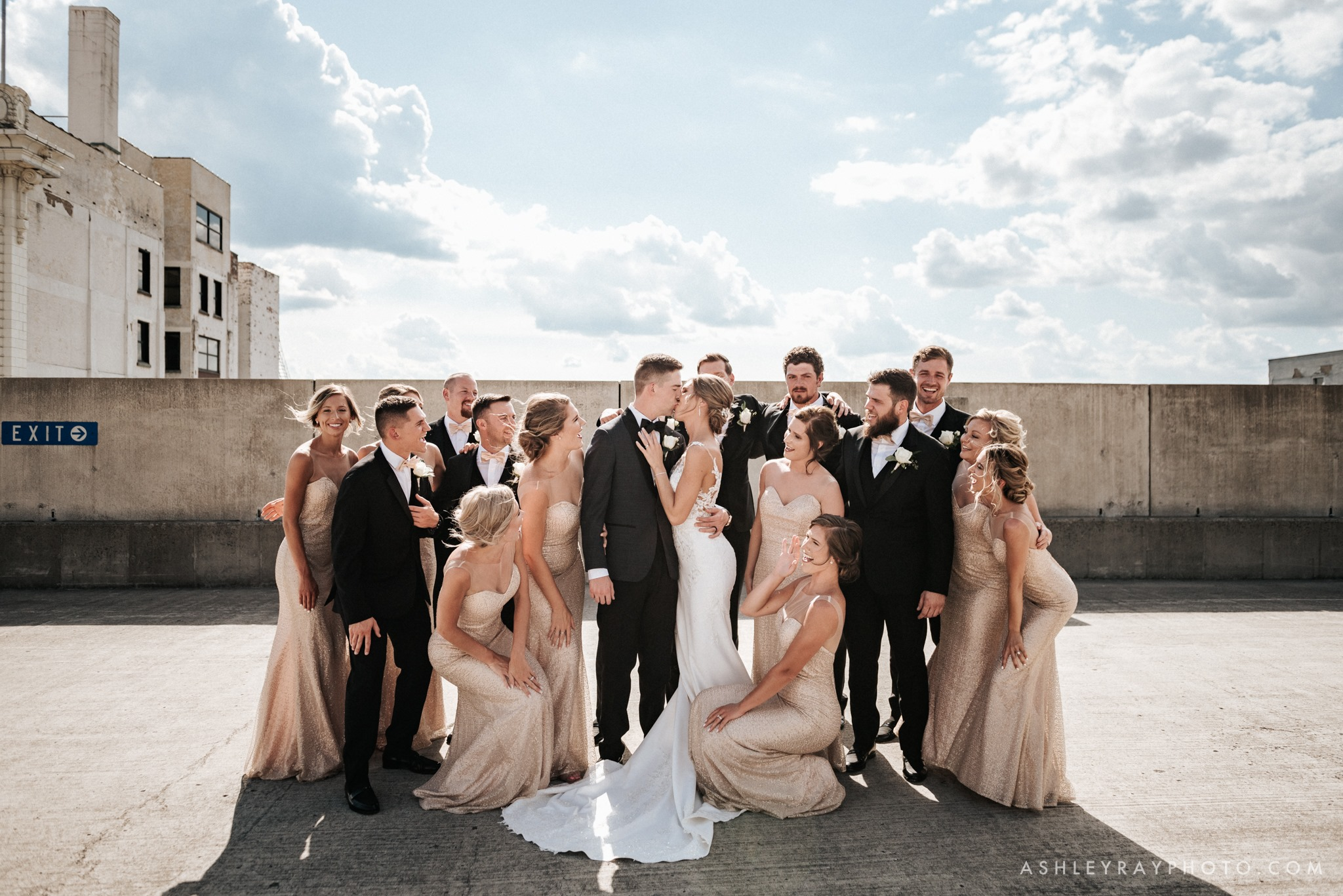 A bride and groom kissing as the bridesmaid and the groomsmen surround them