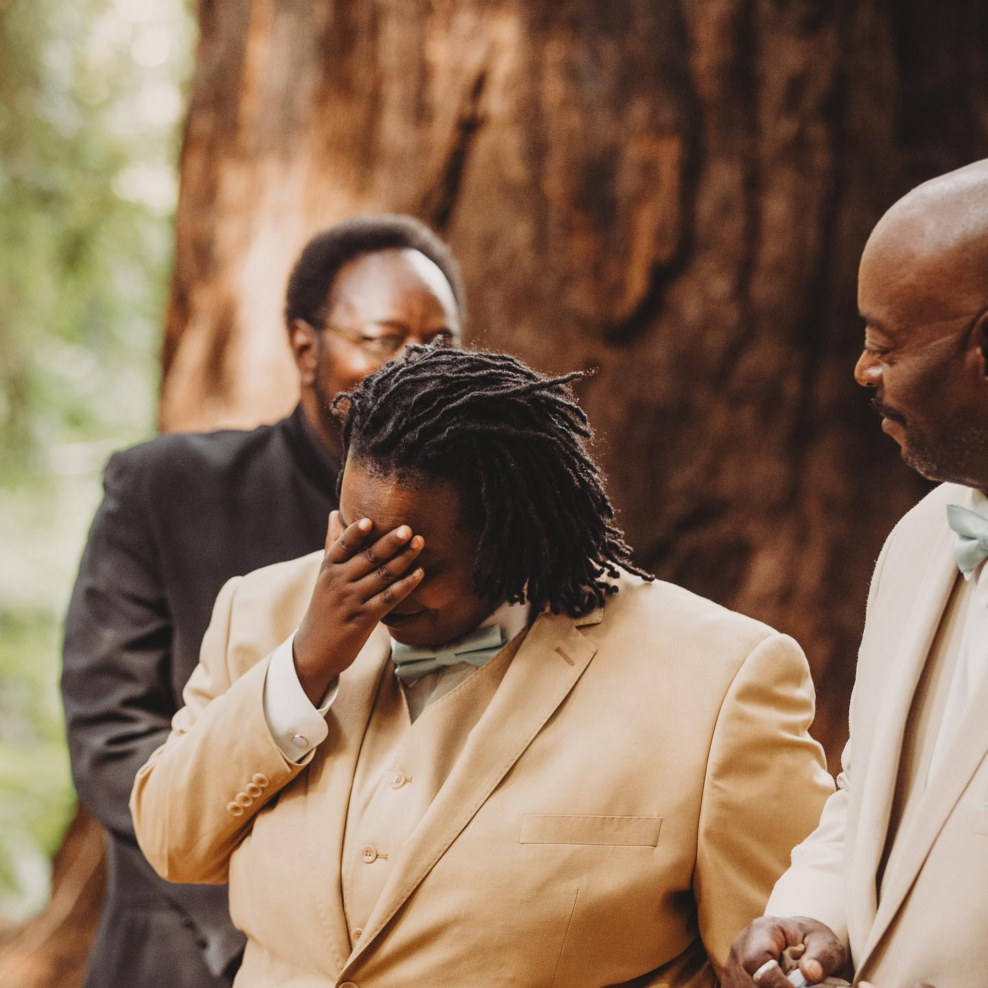 A portrait of a person of color getting emotional at a wedding