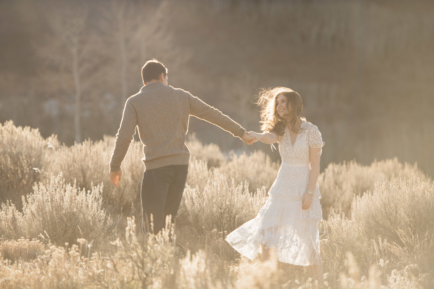 A couple holding hands at a field
